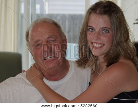 Affectionate Grandaughter Sitting On Grandfather's Lap