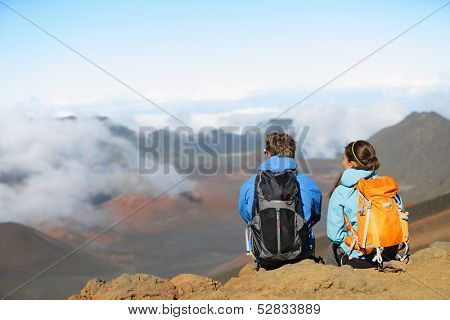 Hiking - hikers sitting enjoying view on volcano. Hiker couple looking at beautiful nature landscape of mountain, East Maui Volcano, Haleakala national park Hawaii, USA. People resting and relaxing.