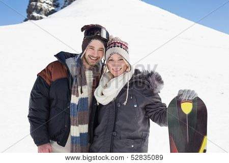 Portrait of a smiling couple in jackets with ski board standing on snow covered landscape