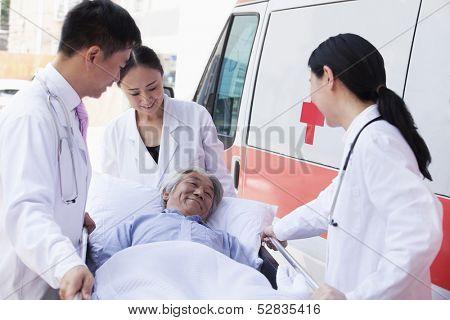 Three doctors wheeling in elderly patient on stretcher
