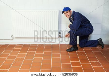 Handyman in blue boiler suit repairing a radiator smiling at camera in bright room