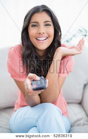 Gleeful cute brunette sitting on couch holding remote in bright living room