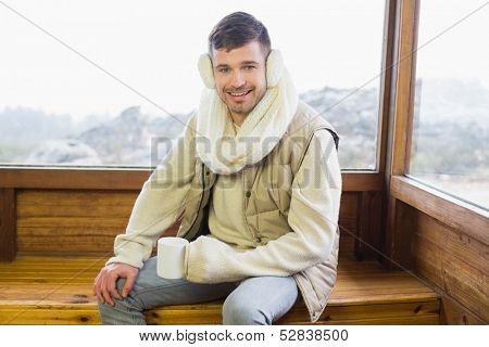 Portrait of a smiling young man wearing earmuff with coffee cup against cabin window