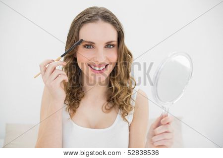Woman using an eyebrow pen and smiling into the camera wile holding a mirror