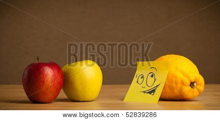 Lemon with sticky post-it note reacting at apples