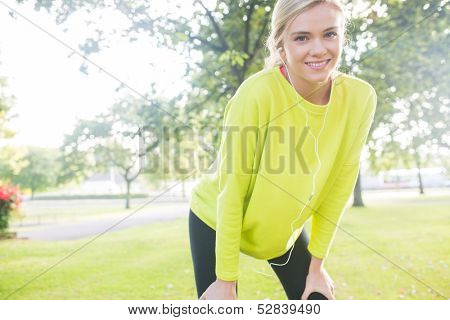 Active cheerful blonde pausing after a run in a park on a sunny day