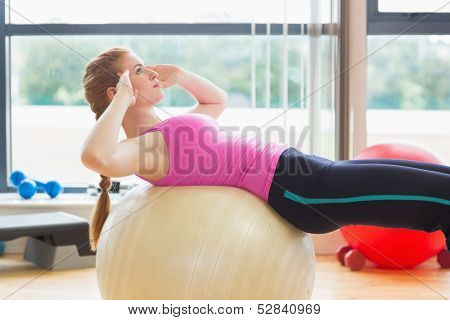 Side view of a fit young woman working out with exercise ball in fitness studio