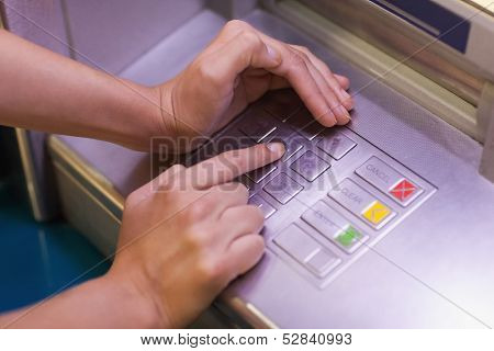 Close up of hand entering pin at an ATM