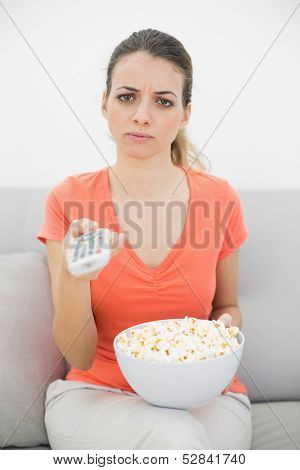 Irritated young woman watching television sitting on couch holding the remote control