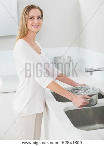 Cheerful gorgeous woman filling pan with water in bright kitchen