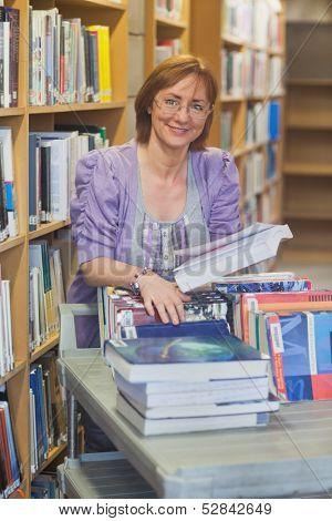 Content calm female librarian returning books smiling at camera