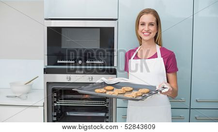 Casual gleeful woman holding baking tray with cookies in bright kitchen