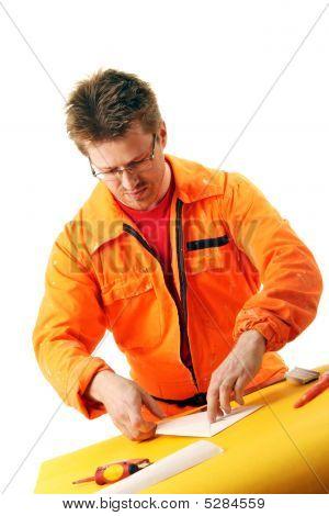 Worker Folds A Paper Sheet