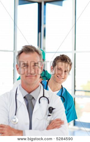 Smiling Young Doctor In Focus In A Line With Copy-space