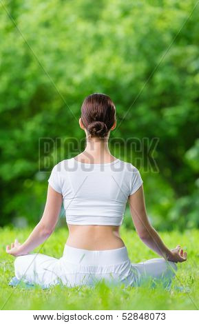 Backview of woman who sits in asana position zen gesturing. Concept of healthy lifestyle and relaxation