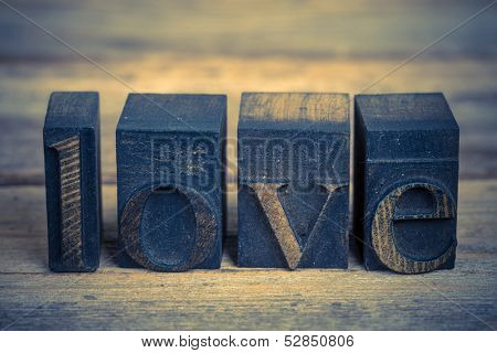The word LOVE wriiten with vintage printing blooks over old wood background