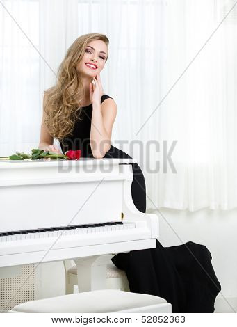 Full-length portrait of woman in black dress standing near the piano with red rose on it. Concept of music and creative hobby