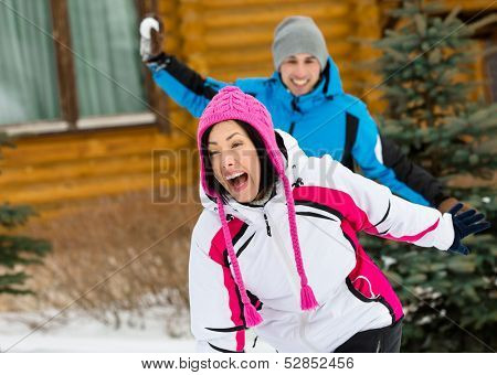 Happy couple having fun outdoors during winter holidays and playing at snowballs