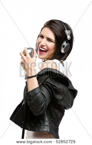 Half-length portrait of rock musician with earphones wearing leather jacket and keeping static mic, isolated on white. Concept of rock music and rave