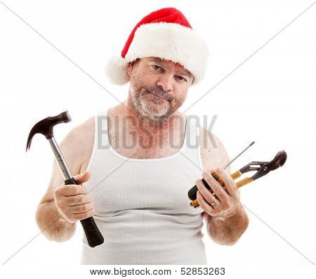 Frustrated dad in a Santa hat holding his tools.  He looks scruffy, like he's been up all night assembling Christmas presents.  Isolated on white.
