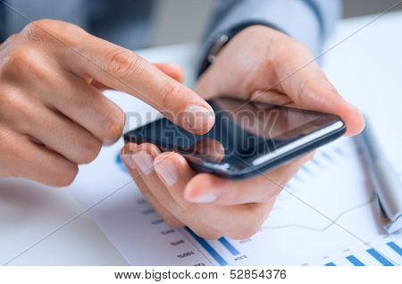 Close Up Of A Businessman's Hand Over Documents Using Smart Phone