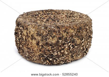 a handmade spice-coated cheese from Spain, on a white background