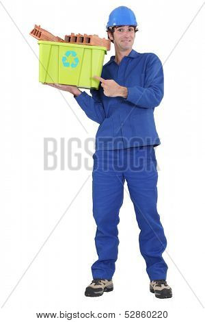 Eager tradesman pointing to a recycling bin