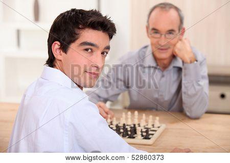 Young man playing chess with his grandfather