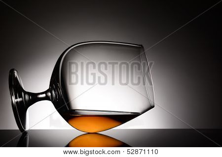 Closeup of a brandy snifter laying on it side. Horizontal format with a light to dark gray spot background. The glass is on a shiny black reflective surface.