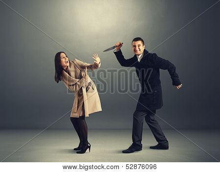 funny maniac with knife attacking startled beautiful woman