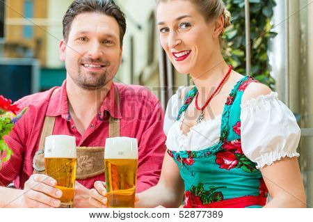 Young couple in traditional Bavarian Tracht in restaurant or pub with beer