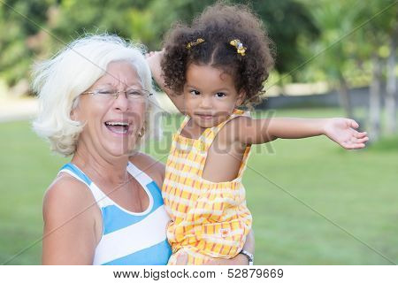 Latin girl and her caucasian grandmother hugging and having fun in a park