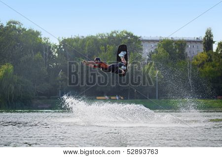 MOSCOW - JUL 13: While wakeboarding man jumping over the waves on a board on the river in Sokolniki on July 13, 2013 in Moscow, Russia.