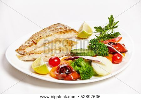 Hake filet grille with steamed vegetables on a plate in a restaurant