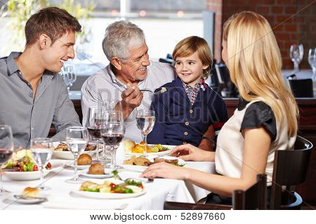 Happy grandfather feeding his grandson in a restaurant