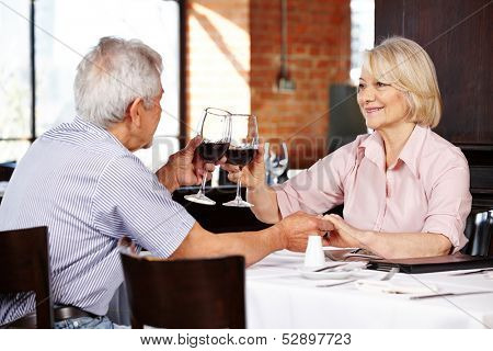 Elderly couple clink glasses with red wine in a restaurant