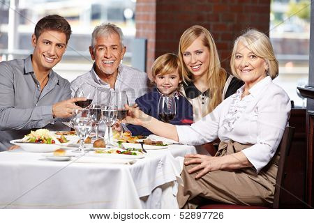 Happy family with child clinking glasses in a restaurant