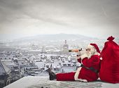 stock photo of spyglass  - Santa Claus sitting over the city looking through spyglass - JPG