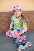 Girl in a helmet and the protection of the hands and feet sit on the floor in roller skates