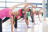 stock photo of young woman posing the camera  - Portrait of smiling women doing the side plank yoga pose at yoga class in fitness studio - JPG