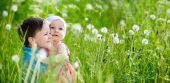 stock photo of summer fun  - Brother and little sister playing in green grass at sunny summer day - JPG
