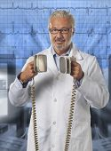 picture of defibrillator  - a doctor using a defibrillator with out of focus background - JPG