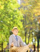 picture of stressless  - Senior gentleman meditating seated on a green grass in a park - JPG