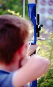 stock photo of fletching  - Boy archer with selective focus on bow sight - JPG