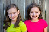 Happy twin sisters with different hairstyle smiling on wood backyard fence