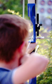 pic of fletching  - Boy archer with selective focus on bow sight - JPG