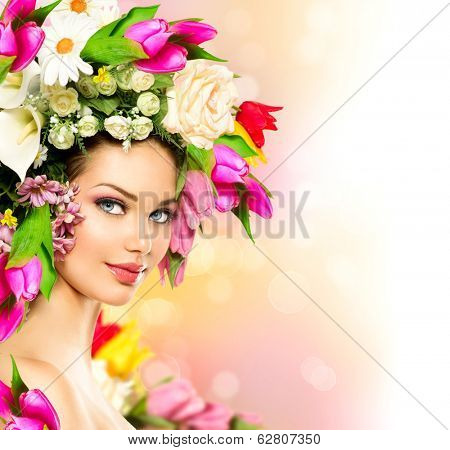 Spring Woman. Beauty Summer model girl with colorful Flowers Hair Style. Beautiful Lady with Blooming flowers on her head. Nature Hairstyle. Holiday Creative Fashion Makeup. Make up