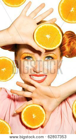 Beauty Model Girl takes Juicy Oranges. Beautiful Joyful teen girl with freckles, funny red hairstyle and yellow makeup . Professional make up. Orange  Slices. Diet