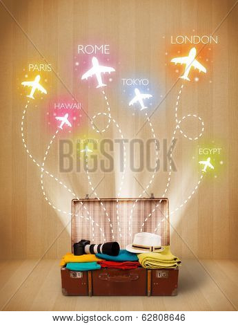 Travel bag with clothes and colorful planes flying out on grungy background