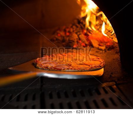 Ready pizza getting from oven